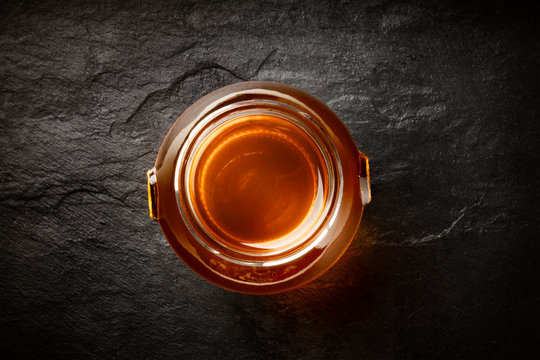 A photo of a vibrant jar of organic honey, shot from above on a black background with copy space