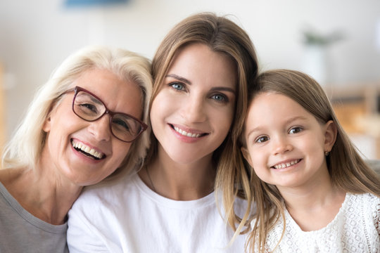 Headshot portrait of three 3 generations family, smiling grandmother, grown young daughter and child girl looking at camera, happy kid granddaughter, mother and old aged grandma posing together