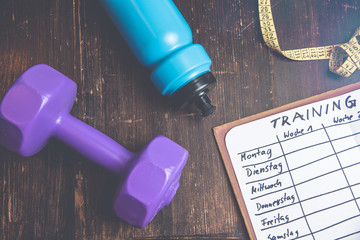 High Angle View Of A Workout Plan In Notebook At Wooden Desk