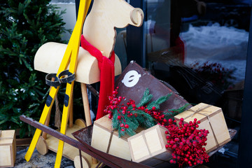 Christmas decoration with sleigh, wooden deer, yellow skiing, gift boxes and christmas tree near window shop