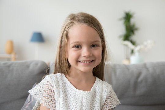 Adorable little girl looking at camera sitting on couch at home, smiling  preschool pretty child with beautiful happy face posing alone on sofa, cute positive cheerful kid headshot portrait