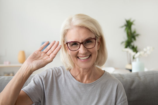 Smiling middle aged woman waving hand looking at camera, older mature lady in glasses making video blog or call at home, happy friendly senior vlogger sitting on sofa dating online, headshot portrait