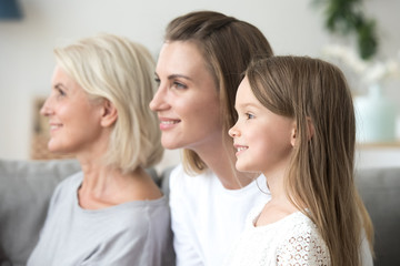Smiling beautiful women in three generation family looking forward thinking of bright future, happy grandmother young mother and little child daughter dream of good, growing up, aging process concept