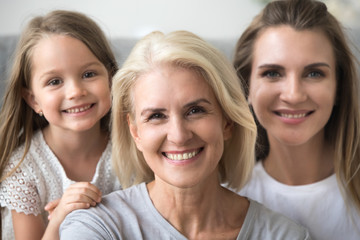 Smiling senior grandmother looking at camera with young daughter and kid granddaughter at background, older grandma in three 3 women happy loving family, older elderly generation concept, portrait