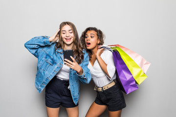 Portrait of surprised young two ladies friends with bright makeup lips standing over grey wall and posing with shopping bags using mobile phone.