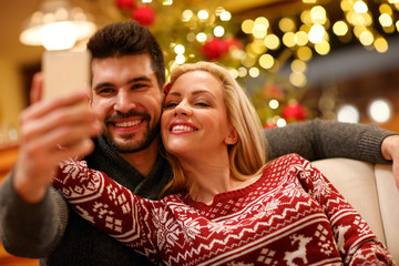 couple in warm sweaters taking selfie picture with smartphone at home.