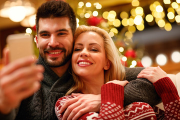 lovely couple taking selfie with smartphone on Christmas .