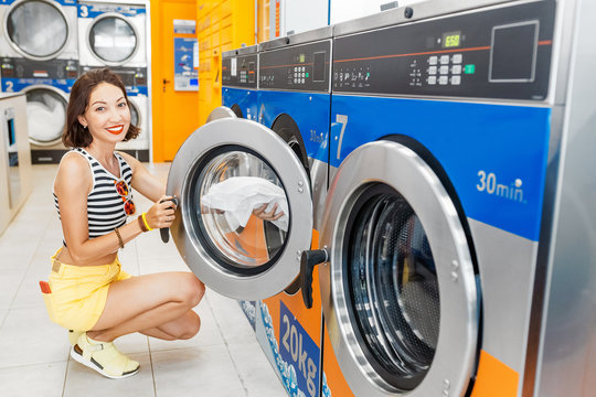 Young woman loading dirty clothes in washing machine in laundromat, laundry service concept