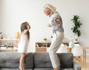 Cute little girl having fun playing with smiling grandmother jumping on couch together, happy granny and active kid grandchild dancing on sofa, grandma and granddaughter laughing playing at home