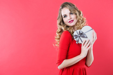 Beautiful woman in a red dress with a gift box.