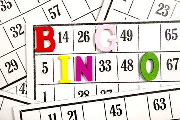 The word bingo made of wooden letters on bingo cards background.