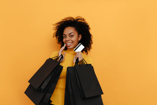 Black friday. Shopping. Afro American girl in yellow sweater is holding shopping bags and a credit card and smiling, on a yellow background