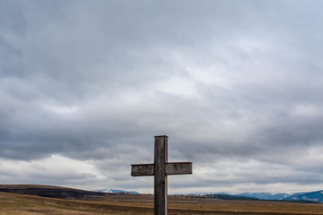 Simple oak catholic cross on focus, dramatic storm clouds, blue mountains with snow on the background.