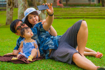 young happy loving Asian Korean family with parents and sweet baby daughter at city park together with father taking selfie pic with mobile phone