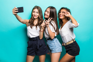 Low angle side view portrait of pretty charming three girls in jeans shorts skirt shooting selfie on front camera using smart phone gesturing v-sign isolated on blue background.