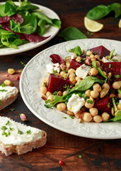 Healthy Beet Salad with chickpeas, pistachios nuts, feta and melted cheese toast on rustic wooden background