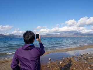 スマートホンで風景を撮影する男性 一人旅 SNS イメージ