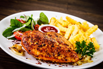 Grilled chicken fillet with french fries on wooden table