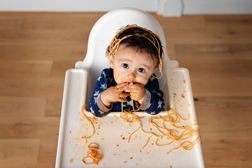 Overhead view of baby making mess with spaghetti in high chair
