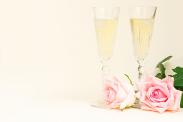Pink blooming fresh valentines day roses with two glasses of cold champagne with copy space