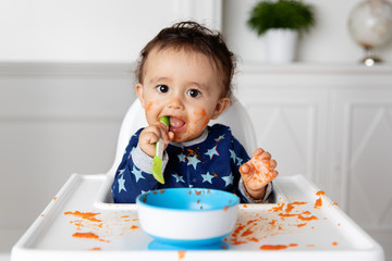 Cute baby eating carrot puree in high chair