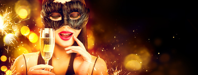 Christmas and New Year holiday celebration. Beauty woman celebrating with champagne, wearing carnival mask. Party, drinking champagne over holiday glowing background