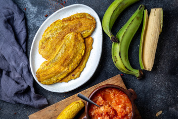 COLOMBIAN CARIBBEAN CENTRAL AMERICAN FOOD. Patacon or toston, fried and flattened whole green plantain banana on white plate with tomato sauce and chicharron Black background, top view Wall mural