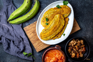 COLOMBIAN CARIBBEAN CENTRAL AMERICAN FOOD. Patacon or toston, fried and flattened whole green plantain banana on white plate with tomato sauce and chicharron Black background, top view
