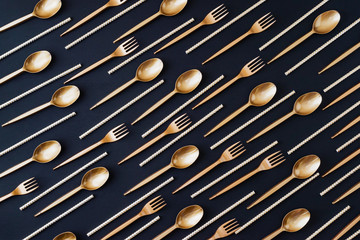 Party decoration background. Golden disposable dishes on dark wooden background