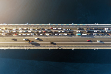 Aerial view of road bridge across river with heavy traffic jam in one direction. Rush hour with...