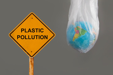 globe in plastic bag with warning sign message PLASTIC POLLUTION , environment problem concept