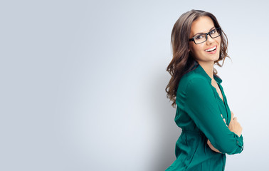 Happy smiling business woman in glasses, on grey