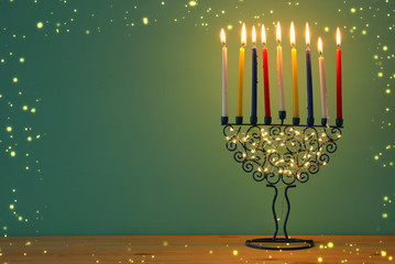image of jewish holiday Hanukkah background with menorah (traditional candelabra) and colorful candles.