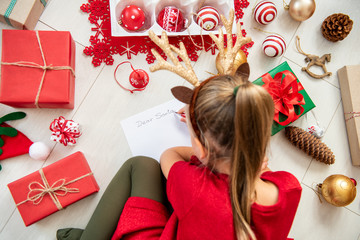Cute girl writing letter to Santa on livingroom floor. Overhead view of a young girl writing her christmas wishlist.