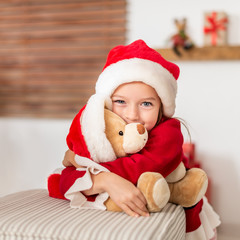 Cute young girl wearing santa hat hugging her christmas present, soft toy teddy bear. Happy kid with xmas present, smiling and looking at camera.