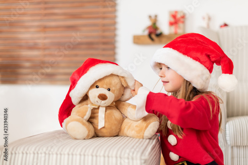 861f28765440c Cute young girl wearing santa hat playing with her christmas present ...