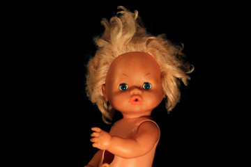 Portrait of an old doll on a black background. Plastic doll face in darkness.