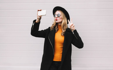 Fashion, technology and people concept - cool girl taking selfie picture by smartphone, elegant female model blowing red lips sends an air kiss posing in city on gray wall background
