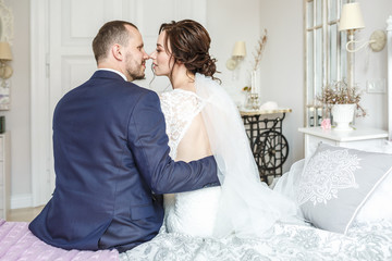young beautiful girl bride sits on a bed with groom