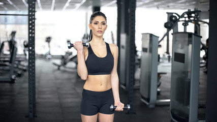 Fit woman lifting dumbbells in gym, arm muscles training, sportive lifestyle
