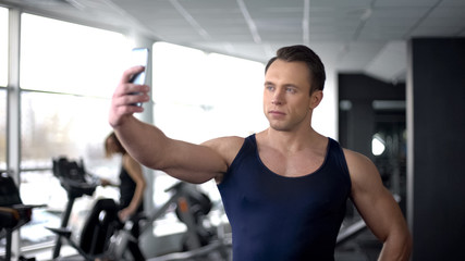 Bodybuilder taking selfie in gym and sending by smartphone, modern technology