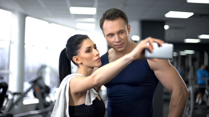 Young man and woman taking selfie in gym, modern technology, social networking