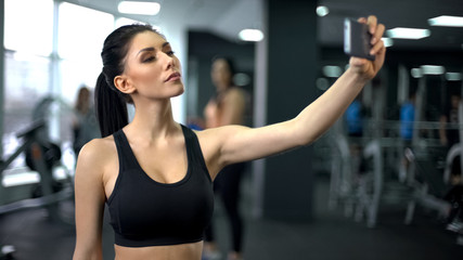 Young sport woman taking selfie after gym workout, social media platform