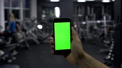 Sportsman checking online smartphone application, monitoring pulse, green screen