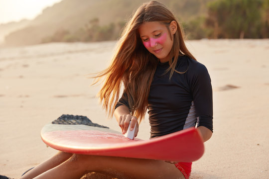 Photo of pretty woman has pink mask on face, waxes surface of her boad before surfing, sits at warm sand ay coast, has sporty body shape, likes sport and recreational activities in open air.