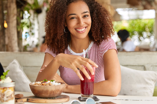 Photo of pleasant looking Afro American woman enjoys time at cafeteria, drinks fresh fruit smoothie, sits at comfortable sofa, has broad smile, waits for friend, eats delicious exotic salad.