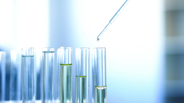 Chemical liquid dripping from pipette in lab tubes, checking reaction, research