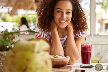 Photo of pleased dark skinned girl smiles positively at camera, spends free time in cafeteria, drinks cocktail, has curly hair, tastes local cuisine, likes to be photographed. People and lunch concept