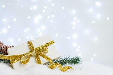 White christmas. gift box with fir tree and decorations in snow, bokeh lights in background