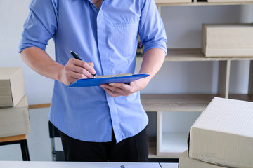 Young male business owner working at home checking box delivery to the customer.